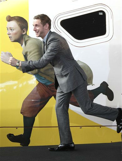 British actor Jamie Bell poses next to Belgian cartoon hero Tintin, depicted on a special high speed Thalys train boarding for Paris, after he and movie director Steven Spielberg attended the world premiere of the Belgian cartoon hero Tintin movie &#34;The Adventures of Tintin: Secret of the Unicorn&#34;, in Brussels, Saturday, Oct. 22, 2011. &#40;AP Photo&#47;Yves Logghe&#41; <span class=meta>(AP Photo&#47; Yves Logghe)</span>