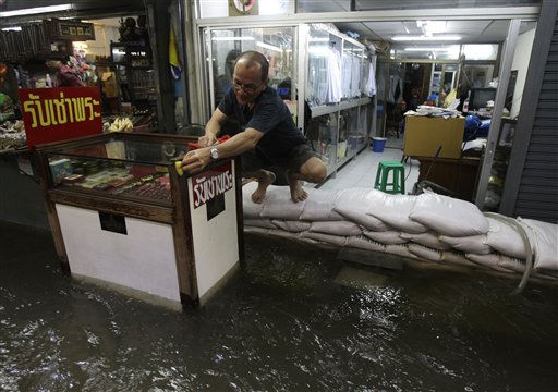 A Thai store owner sits on sandbags as he cleans his display cabinet at a flooded amulet market beside a swollen river in Bangkok, Thailand on Sunday Oct. 23, 2011. The threat that floodwaters will inundate Thailand&#39;s capital could ease by the beginning of next month as record-high levels in the river carrying torrents of water downstream from the country&#39;s north begin to decline, authorities said Sunday. &#40;AP Photo&#47;Aaron Favila&#41; <span class=meta>(AP Photo&#47; Aaron Favila)</span>