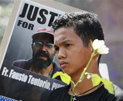A sympathizer holds a white rose next to a portrait of slain Italian missionary Rev. Fausto &#34;Pops&#34; Tentorio during a protest near the Presidential Palace in Manila to demand justice as he is laid to rest Tuesday Oct. 25, 2011 in Kidapawan, North Cotabato province in southern Philippines. Rev. Tentorio, of Italy&#39;s Pontifical Institute for Foreign Missions &#40;PIME&#41; was killed last Monday inside his parish compound in north Cotabato&#39;s Arakan township. &#40;AP Photo&#47;Bullit Marquez&#41; <span class=meta>(AP Photo&#47; Bullit Marquez)</span>