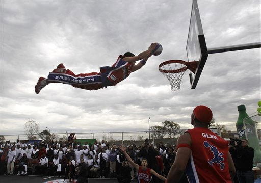 Chad Layton, a member of the Detroit Pistons Flight Crew, performs an aerial dunk on the Highland Park Community High School&#39;s refurbished basketball court, Tuesday, Oct. 25, 2011, in Highland Park, Mich. The Pistons helped refurbish the school&#39;s outdoor basketball courts with help from a Sprite Spark Parks grant. &#40;AP Photo&#47;Carlos Osorio&#41; <span class=meta>(AP Photo&#47; Carlos Osorio)</span>