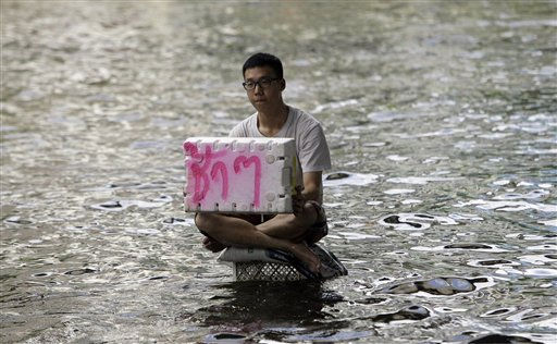 A Thai resident sits on a plastic basket in floodwaters and holds a sigh meaning &#34;drive slow&#34; in Thai in Bangkok, Thailand, Wednesday, Oct. 26, 2011. Floodwaters inched closer to a terminal at the Thai capital&#39;s second largest airport Wednesday, leading many who had sought refuge at a shelter there to flee amid warnings that parts of Bangkok could be inundated by up to 5 feet &#40;1.5 meters&#41; of water.&#40;AP Photo&#47;Sakchai Lalit&#41; <span class=meta>(AP Photo&#47; Sakchai Lalit)</span>