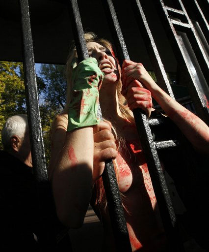 Secury guards detain an activist of the Ukrainian female rights organization &#34;Femen&#34;, during an action of nude protest in front of Kiev Zoo, Ukraine, Thursday, Oct. 27, 2011. Kiev zoo is a place that Femen&#39;s activists compared to a concentration camp for those with fur and feathers. Hundreds of animals died at the zoo in recent years due to malnutrition, lack of medical care and abuse, and some suspect that corruption is at the heart of the problem. Femen calls for the 100-year-old zoo to be closed and its animals sent to other European countries. &#40;AP Photo&#47;Efrem Lukatsky&#41; <span class=meta>(AP Photo&#47; Efrem Lukatsky)</span>
