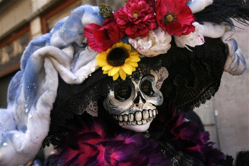 A woman dressed as traditional Mexican &#34;Catrina&#34; walks through downtown for Day of the Dead celebrations in Mexico City, Sunday Oct. 30, 2011. Mexicans celebrate Day of the Dead to honor deceased loved ones, a tradition that coincides with All Saints Day and All Souls Day on Nov. 1 and 2. &#40;AP Photo&#47;Marco Ugarte&#41; <span class=meta>(AP Photo&#47; Marco Ugarte)</span>