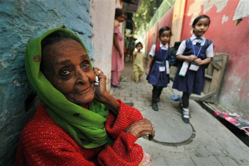 An Indian elderly woman sits in front of her house as children arrive from school on a street in Lucknow, India, Monday, Oct. 31, 2011. According to the U.N. Population Fund, there will be a symbolic &#34;seven billionth&#34; baby sharing Earth&#39;s land and resources on Oct. 31. Already the second most populous country with 1.2 billion people, India is expected to overtake China around 2030 when its population soars to an estimated 1.6 billion. &#40;AP Photo&#47;Rajesh Kumar Singh&#41; <span class=meta>(AP Photo&#47; Rajesh Kumar Singh)</span>
