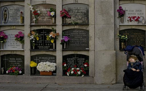 "<div class=""meta ""><span class=""caption-text "">A child sleeps in a baby carriage next to the tomb of her relatives on the eve of 'All Saints Day',  in the public cemetery, in Pamplona northern Spain, Monday Oct 31, 2011. All Saints Day which falls on Nov. 1, is a Catholic holiday to reflect on the saints and deceased relatives. (AP Photo/Alvaro Barrientos) (AP Photo/ Alvaro Barrientos)</span></div>"