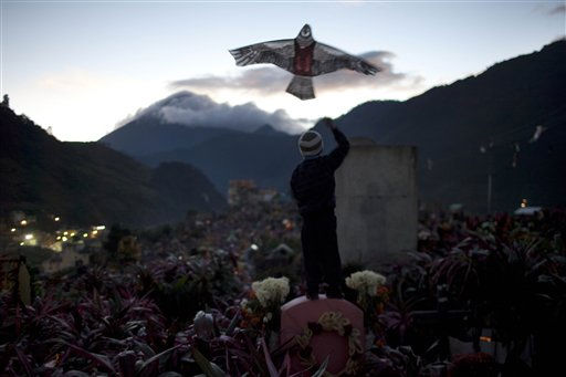 A boy flies a kite in the cemetery on Day of the Dead in Zunil, Guatemala, Tuesday Nov. 1, 2011.  Because Mayans believe the dead are allowed to visit their families on earth for one day, family members fly kites to guide their departed relatives to their earthly homes.  Also decorating graves with fresh flowers is common throughout Latin America, as is having a picnic at the departed relative&#39;s grave site. &#40;AP Photo&#47;Rodrigo Abd&#41; <span class=meta>(AP Photo&#47; Rodrigo Abd)</span>