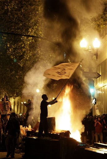 An Occupy Oakland protester waves a flag next to a bonfire in Oakland, Calif., Thursday, Nov. 3, 2011. &#40;AP Photo&#47;Jeff Chiu&#41; <span class=meta>(AP Photo&#47; Jeff Chiu)</span>