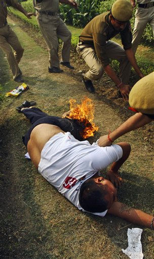 Indian police officers try to put out fire engulfing from the trousers of an exile Tibetan in New Delhi, India, Friday, Nov. 4, 2011. The Tibetan exile set himself on fire outside the Chinese Embassy as a show of solidarity following recent self-immolation protests by Tibetans against the Chinese government. &#40;AP Photo&#41; <span class=meta>(AP Photo&#47; Anonymous)</span>