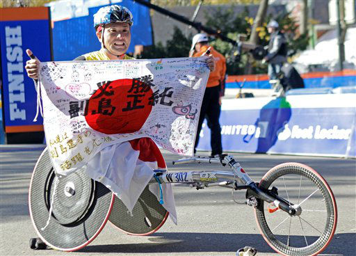 Masazumi Soejima, of Japan, holds up a flag after winning the men&#39;s wheelchair division of the  New York City Marathon in New York, Sunday, Nov. 6, 2011. &#40;AP Photo&#47;Kathy Willens&#41; <span class=meta>(AP Photo&#47; Kathy Willens)</span>