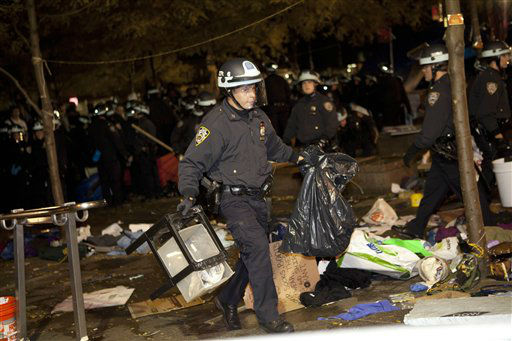 A police officer carries trash through Zuccotti Park, the longtime encampment for Occupy Wall Street protesters in New York, as the cleanup effort begins early Tuesday, Nov. 15, 2011. At about 1 a.m. Tuesday, police handed out notices from the park&#39;s owner, Brookfield Office Properties, and the city saying that the park had to be cleared because it had become unsanitary and hazardous. Protesters were told they could return, but without sleeping bags, tarps or tents. &#40;AP Photo&#47;John Minchillo&#41; <span class=meta>(AP Photo&#47; John Minchillo)</span>