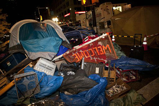 "<div class=""meta ""><span class=""caption-text "">Trash is piled high near Zuccotti Park, Occupy Wall Street's longtime encampment in New York, during the cleanup effort early Tuesday, Nov. 15, 2011. At about 1 a.m. Tuesday, police handed out notices from the park's owner, Brookfield Office Properties, and the city saying that the park had to be cleared because it had become unsanitary and hazardous. Protesters were told they could return, but without sleeping bags, tarps or tents. (AP Photo/John Minchillo) (AP Photo/ John Minchillo)</span></div>"