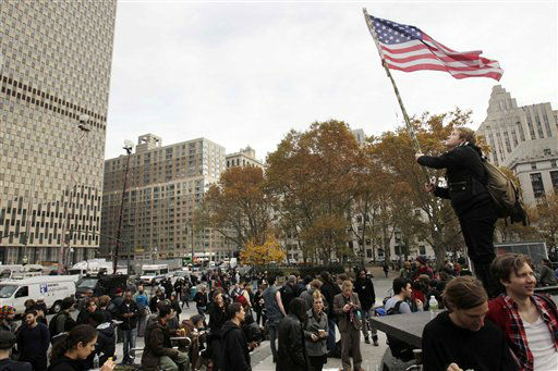 A woman waves an American flag over Occupy Wall Street protesters that gathered in Foley Square in New York, Tuesday, Nov. 15, 2011. Police officers evicted Occupy Wall Street protesters from the park overnight.   The National Lawyers Guild obtained a court order allowing the protesters to return with their tents to the park, where they have camped for two months. The guild said the injunction prevents the city from enforcing park rules on the protesters.  &#40;AP Photo&#47;Seth Wenig&#41; <span class=meta>(AP Photo&#47; Seth Wenig)</span>