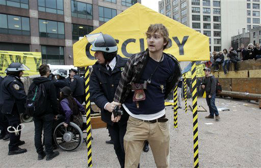 "<div class=""meta image-caption""><div class=""origin-logo origin-image ""><span></span></div><span class=""caption-text"">Police make an arrest after entering an enclosed site near Canal Street where Occupy Wall Street protesters gathered on Tuesday, Nov. 15, 2011.  Protesters vowed to regroup after an early morning police raid removed their encampment from Zuccotti Park.  Hundreds of police officers in riot gear before dawn Tuesday raided the New York City park where the Occupy Wall Street protests began, evicting and arresting hundreds of protesters from what has become the epicenter of the worldwide movement protesting corporate greed and economic inequality.  (AP Photo/Seth Wenig) (AP Photo/ Seth Wenig)</span></div>"