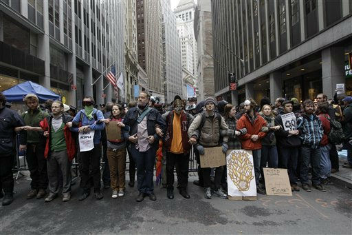 The New York Stock Exchange is seen in the background as demonstrators affiliated with the Occupy Wall Street movement lock arms as they block Broad Street, Thursday, Nov. 17, 2011 in New York.  &#40;AP Photo&#47;Mary Altaffer&#41; <span class=meta>(AP Photo&#47; Mary Altaffer)</span>