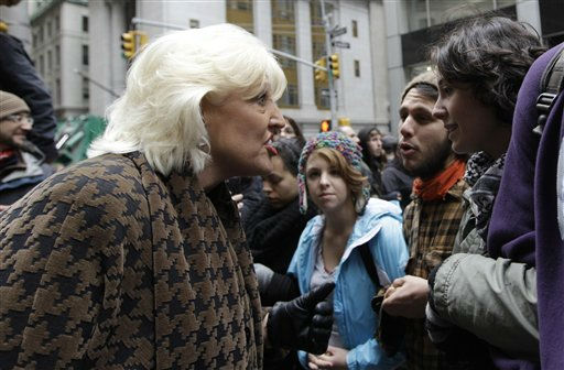 A woman argues with demonstrators affiliated with the Occupy Wall Street movement lock arms as they block Broad Street, Thursday, Nov. 17, 2011 in New York.   Two days after the encampment that sparked the global Occupy protest movement was cleared by authorities, demonstrators marched through New York&#39;s financial district  and promised a national day of action with mass gatherings in other cities.   &#40;AP Photo&#47;Mary Altaffer&#41; <span class=meta>(AP Photo&#47; Mary Altaffer)</span>