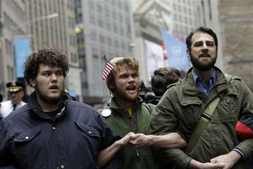 The New York Stock Exchange is seen in the background as Occupy Wall Street demonstrators William Harkins, left, of Boston, Austin Rose, center, of Portland, Ore., and Matthew Karges, of Brooklyn, lock arms as they block Broad Street, Thursday, Nov. 17, 2011 in New York.   Two days after the encampment that sparked the global Occupy protest movement was cleared by authorities, demonstrators marched through New York&#39;s financial district  and promised a national day of action with mass gatherings in other cities.  &#40;AP Photo&#47;Mary Altaffer&#41; <span class=meta>(AP Photo&#47; Mary Altaffer)</span>