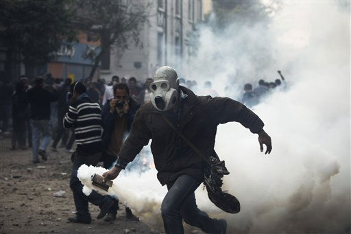 A protester throws a gas canister towards Egyptian riot police, not seen, near the interior ministry during clashes in downtown Cairo, Egypt, Sunday, Nov. 20, 2011. Firing tear gas and rubber bullets, Egyptian riot police on Sunday clashed for a second day with thousands of rock-throwing protesters demanding that the ruling military quickly announce a date to hand over power to an elected government. &#40;AP Photo&#47;Tara Todras-Whitehill&#41; <span class=meta>(AP Photo&#47; Tara Todras-Whitehill)</span>