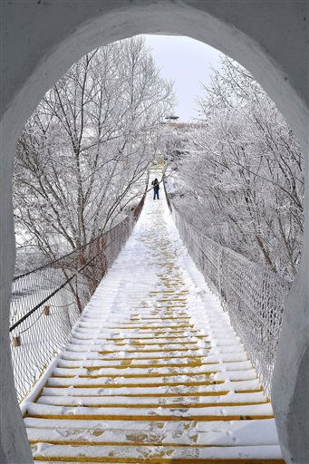 In this Sunday Nov. 20, 2011 photo, a tourist walks on a bridge after a snow in the Greater Hinggan Mountains in Hulunbuir City, in northern China&#39;s Inner Mongolia Region. &#40;AP Photo&#41; CHINA OUT <span class=meta>(AP Photo&#47; Anonymous)</span>