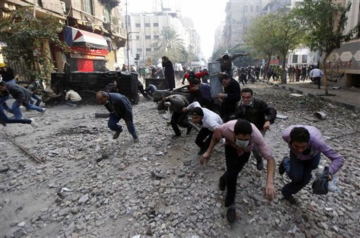 "<div class=""meta ""><span class=""caption-text "">Protesters run for cover during clashes with the Egyptian riot police near Tahrir square in Cairo, Egypt, Tuesday, Nov. 22, 2011. Egypt's civilian Cabinet has offered to resign after three days of violent clashes in many cities between demonstrators and security forces, but the action failed to satisfy protesters deeply frustrated with the new military rulers. (AP Photo/Khalil Hamra) (AP Photo/ Khalil Hamra)</span></div>"