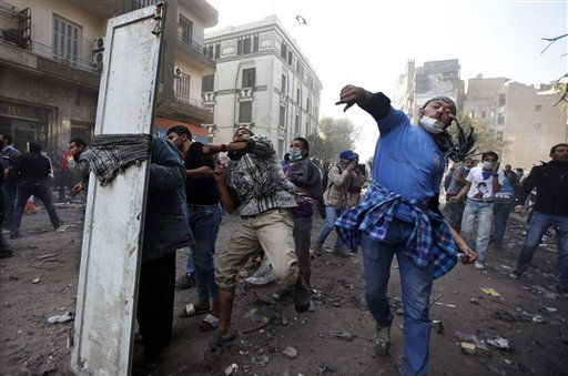 "<div class=""meta image-caption""><div class=""origin-logo origin-image ""><span></span></div><span class=""caption-text"">Egyptian protesters clash with security forces near Tahrir Square in Cairo, Egypt, Wednesday, Nov. 23, 2011. Egyptian police are clashing with anti-government protesters for a fifth day in Cairo. Tens of thousands of protesters in Tahrir Square have rejected a promise by Egypt's military ruler to speed up a presidential election to the first half of next year. They want Field Marshal Hussein Tantawi to step down immediately in favor of an interim civilian council. (AP Photo/Khalil Hamra) (AP Photo/ Khalil Hamra)</span></div>"