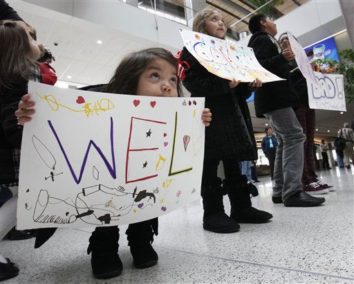 Kaitlyn Medina, 3, peers over her welcome sign as she tries to spot her father, Jose Medina, who was arriving at the Sacramento International Airport in Sacramento, Calif., Wednesday Nov. 23, 2011.  Medina, who returned from Wisconsin where he had been working the past month,  to find his children, Kaitlyn and her siblings, Krystal, 6, second from left,  Mario, 11, third from left, and Briana, anxiously awaiting his return for Thanksgiving.&#40;AP Photo&#47;Rich Pedroncelli&#41; <span class=meta>(AP Photo&#47; Rich Pedroncelli)</span>