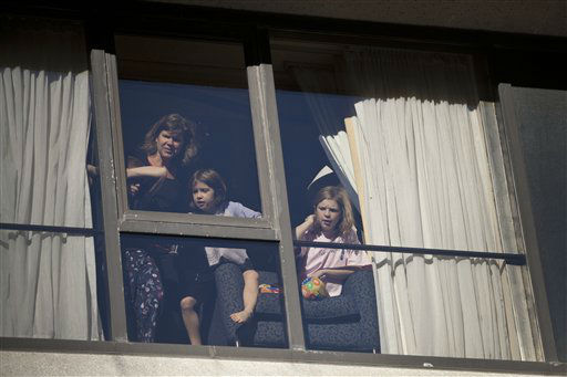 A family watches the Macy&#39;s Thanksgiving Day Parade from their hotel room in Time Square in New York on Thursday, Nov. 24, 2011. The parade premiered in 1924, this is its 85th year. &#40;AP Photo&#47;Andrew Burton&#41; <span class=meta>(AP Photo&#47; Andrew Burton)</span>