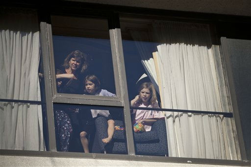 A family watches the Macy&#39;s Thanksgiving Day Parade from their hotel room in Times Square in New York on Thursday, Nov. 24, 2011. The parade premiered in 1924, this is its 85th year. &#40;AP Photo&#47;Andrew Burton&#41; <span class=meta>(AP Photo&#47; Andrew Burton)</span>