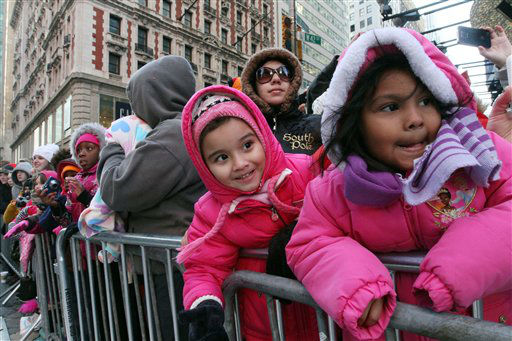 Gaila Reyes, 5, right, and her sister Michele Reyes, 4, second from right, react as they and others watch the 85th Annual Macy&#39;s Thanksgiving Day Parade as it moves across New York&#39;s 42nd Street Thursday Nov. 24, 2011. &#40;AP Photo&#47;Tina Fineberg&#41; <span class=meta>(AP Photo&#47; Tina Fineberg)</span>