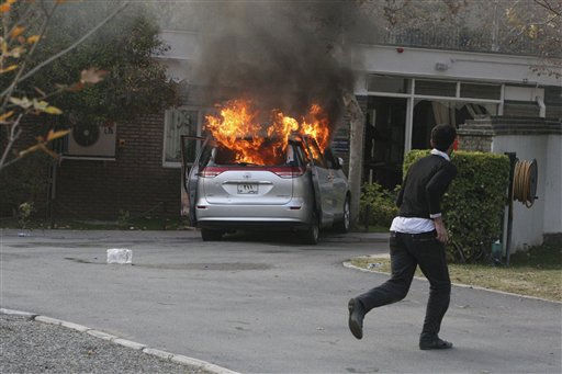 "<div class=""meta ""><span class=""caption-text "">An Iranian hard-line protester runs inside the British Embassy as a diplomatic vehicle is set on fire by demonstrators who stormed the embassy, in Tehran, Iran, Tuesday, Nov. 29, 2011. Dozens of hard-line Iranian students stormed the British Embassy in Tehran on Tuesday, bringing down the Union Jack flag and throwing documents from windows in scenes reminiscent of the anger against Western powers after the 1979 Islamic Revolution. The mob moved into the diplomatic compound two days after Iran's parliament approved a bill that reduces diplomatic relations with Britain following London's support of recently upgraded Western sanctions on Tehran over its disputed nuclear program. (AP Photo/Vahid Salemi) (AP Photo/ Vahid Salemi)</span></div>"