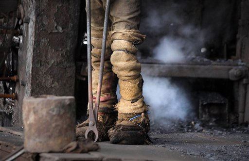 "<div class=""meta ""><span class=""caption-text "">An Indian laborer works in an iron and steel factory on the outskirts of Jammu, India, Thursday, Dec. 1, 2011. India's economic growth skidded to 6.9 percent in the July-September quarter, its lowest in over two years, and is forecast to slow further amid delayed economic reforms and a worsening global outlook.(AP Photo/Channi Anand) (AP Photo/ Channi Anand)</span></div>"
