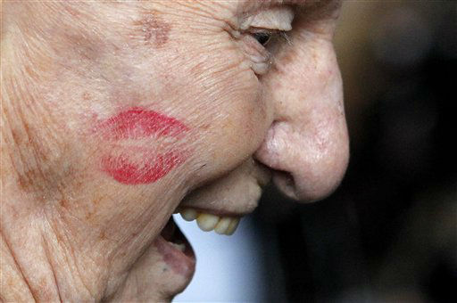 A lipstick mark is seen planted on the cheek of Pearl Harbor survivor James Cook by a member of the Andrews Sisters&#39; styled &#39;Victory Belles,&#39; at a ceremony to observe the 70th anniversary of the attack on Pearl Harbor, at the National World War II Museum in New Orleans, Wednesday, Dec. 7, 2011. &#40;AP Photo&#47;Gerald Herbert&#41; <span class=meta>(AP Photo&#47; Gerald Herbert)</span>