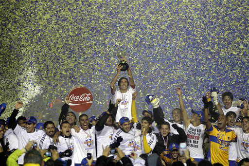 Tigres&#39; Lucas Lobos, center top, holds up the Mexican League soccer championship trophy as he celebrates with teammates the victory 3-1 over Santos de Torreon in Monterrey, Mexico, Sunday, Dec. 11, 2011. &#40;AP Photo&#47;Daniel Jayo&#41; <span class=meta>(AP Photo&#47; Daniel Jayo)</span>