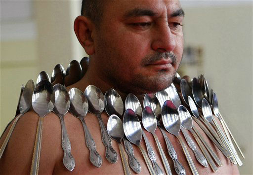Etibar Elchiyev demonstrates his magnetic ability as he poses with 50 metal spoons magnetized to his body during an attempt to break the Guinness World Record for Most Spoons on a Human Body in Tbilisi, Georgia, Wednesday, Dec. 14, 2011. Elchiyev claims that his body acts as a magnet attracting metal objects. &#40;AP Photo&#47;Shakh Aivazov&#41; <span class=meta>(AP Photo&#47; Shakh Aivazov)</span>