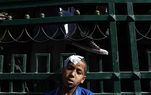 An injured Egyptian youth protester rests after getting first aid care during clashes with army soldiers near Tahrir Square in Cairo, Sunday, Dec. 18, 2011. Egypt&#39;s military sought to isolate pro-democracy activists protesting against their rule, depicting them as conspirators and vandals, as troops and protesters clashed for a third straight day, pelting each other with stones near parliament in the heart of the capital. &#40;AP Photo&#47;Nasser Nasser&#41; <span class=meta>(AP Photo&#47; Nasser Nasser)</span>