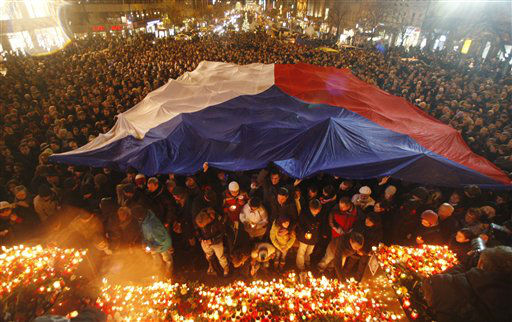People gather under a Czech national flag as thousands mark the passing of former Czech president Vaclav Havel at the Venceslaw&#39;s square in Prague, Czech Republic, Sunday, Dec. 18, 2011. Havel, the dissident playwright who wove theater into politics to peacefully bring down communism in Czechoslovakia and become a hero of the epic struggle that ended the Cold War, died Sunday Dec. 18, 2011 in Prague. He was 75. &#40;AP Photo&#47;Petr David Josek&#41; <span class=meta>(AP Photo&#47; Petr David Josek)</span>