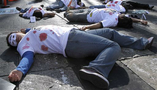 People with masks that read in Spanish &#34;Without name,&#34;  wearing T-shirts with red stains simulating blood, lie on the floor as they participate in a protest of relatives of Mexicans who migrated to the U.S. outside Mexico&#39;s National Migration Institute in Mexico City, Sunday Dec. 18, 2011.  Protesters demanded that Mexico&#39;s authorities do more to guarantee the human rights of migrants in Mexico and the U.S. &#40;AP Photo&#47;Marco Ugarte&#41; <span class=meta>(AP Photo&#47; Marco Ugarte)</span>