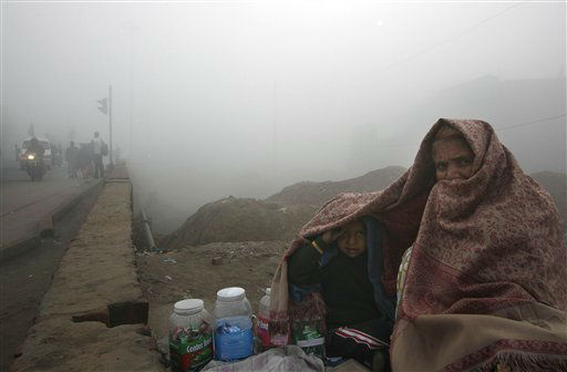 An Indian woman and a young child share a shawl to protect themselves from cold on a foggy morning, in New Delhi, India, Monday, Dec. 19, 2011. &#40;AP Photo&#47;Manish Swarup&#41; <span class=meta>(AP Photo&#47; Manish Swarup)</span>