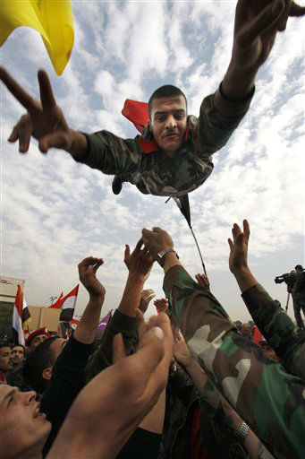 A Syrian solider flashes the victory sign as he is thrown in the air during a rally at Umayyad Square in Damascus, Syria, Wednesday, Dec. 21, 2011. Syrian troops assaulting a northwest town with machine gun fire and shelling have killed dozens in one of the deadliest episodes of the 9-month-old uprising against President Bashar Assad&#39;s regime, activists said Wednesday. &#40;AP Photo&#47; Muzaffar Salman&#41; <span class=meta>(AP Photo&#47; Muzaffar Salman)</span>