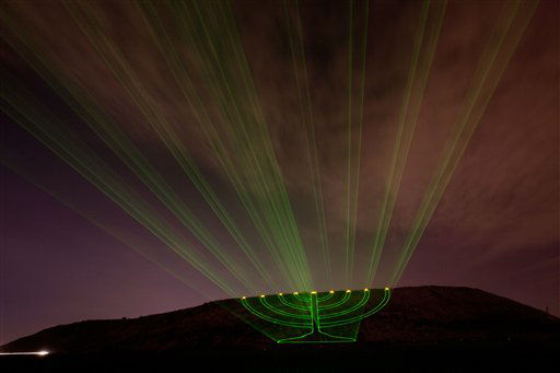 Laser beams creating the image of a large lit Hanukkah menorah are projected on the Hiriya landfill, a former waste disposal site, now called the Ariel Sharon Park, near Tel Aviv, Israel, on the second eve of Hanukkah, Wednesday, Dec. 21, 2011. The Jewish festival of light, an eight-day commemoration of the Jewish uprising in the second century B.C. against the Greek-Syrian kingdom, which had tried to put statues of Greek gods in the Jewish Temple in Jerusalem, started Tuesday. &#40;AP Photo&#47;Ariel Schalit&#41; <span class=meta>(AP Photo&#47; Ariel Schalit)</span>
