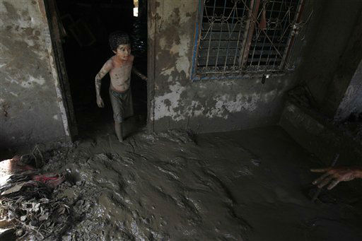 Richard Racadio, 9, an affected resident, cleans up his house which was buried in mud in Friday&#39;s flash flooding brought about by Tropical storm Washi in Iligan city southern Philippines, Wednesday Dec. 21, 2011. The official death toll from last week&#39;s massive flash flooding in two southern Philippine cities topped 1,000 on Wednesday while authorities said they lost count of how many more were missing in one of the worst calamities to hit the coastal region. &#40;AP Photo&#47;Bullit Marquez&#41; <span class=meta>(AP Photo&#47; Bullit Marquez)</span>