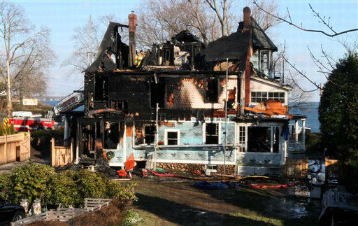 Firefighters investigate a house where an early morning fire left five people dead Sunday, Dec. 25, 2011, in Stamford, Conn. Officials said the fire, which was reported shortly before 5 a.m., killed two adults and three children. Two others escaped. Their names have not been released. &#40;AP Photo&#47;Tina Fineberg&#41; <span class=meta>(AP Photo&#47; Tina Fineberg)</span>