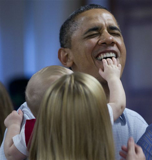 President Barack Obama gets a mouth  full of fingers from Cooper Wall Wagner, 8 months, as he poses for a photo with Coopers and his parents Captain Greg and Meredith Wagner, as he visits members of the military during Christmas dinner at Anderson Hall on Marine Corps Base Hawaii , Sunday, Dec. 25, 2011, in Kaneohe, Hawaii. &#40;AP Photo&#47;Carolyn Kaster&#41; <span class=meta>(AP Photo&#47; Carolyn Kaster)</span>