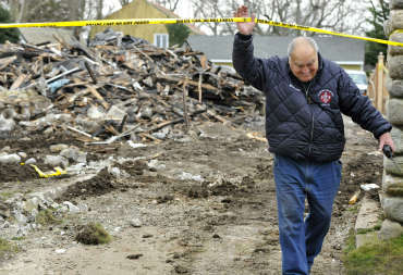 "<div class=""meta ""><span class=""caption-text "">Stamford fire department Lt. Tommy Mardi leaves the charred remains of Madonna Badger's home in Stamford, Conn., Tuesday, Dec. 27, 2011.   A fire killed Badger's three daughters and parents early Christmas morning.  (AP Photo/Jessica Hill) (AP Photo/ Jessica Hill)</span></div>"