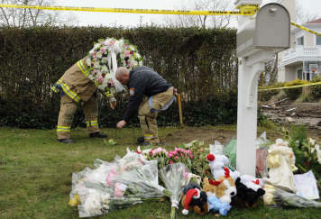 Firefighters lay a wreath in a memorial area outside the home of Madonna Badger in Stamford, Conn., Tuesday, Dec. 27, 2011.  A fire at the home on Christmas morning killed Badger&#39;s three daughters and parents. The Christmas Day fire was a tragic accident related to a fireplace in the home, not the result of foul play, Stamford Mayor Michael Pavia said Tuesday, Dec. 27, 2011. &#40;AP Photo&#47;Jessica Hill&#41; <span class=meta>(AP Photo&#47; Jessica Hill)</span>