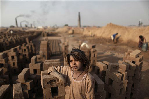 Pakistani girl Shaheen Akram, 7, stands between the bricks where she works with her family in a brick factory on the outskirts of Islamabad, Pakistan, Tuesday, Dec. 27, 2011. &#40;AP Photo&#47;Muhammed Muheisen&#41; <span class=meta>(AP Photo&#47; Muhammed Muheisen)</span>