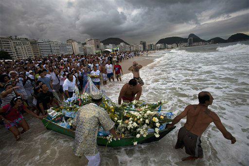 Faithful push a boat filled with flowers into the waters of Copacabana beach as an offering for Yemanja, goddess of the sea, in Rio de Janeiro, Brazil, Thursday Dec. 29, 2011. On New Year&#39;s Eve, Brazilian worshippers of Yemanja celebrate the diety, offerings flowers and launching boats, large and small, into the ocean in exchange for blessings in the new year. The belief in the goddess comes from the African Yoruban religion brought to America by West African slaves. &#40;AP Photo&#47;Victor R. Caivano&#41; <span class=meta>(AP Photo&#47; Victor R. Caivano)</span>