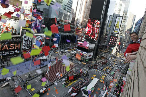 Times Square Alliance President Tim Tompkins throws a handful of confetti from eight stories above onto the streets of Times Square, Thursday, Dec. 29, 2011 in New York. The airworthiness test is in preparation for the release of one ton of confetti by hand from various buildings in Times Square at midnight on New Year?s Eve.?&#40;AP Photo&#47;Mary Altaffer&#41; <span class=meta>(AP Photo&#47; Mary Altaffer)</span>