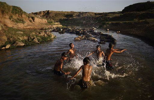 Following their daily work at a wholesale fruit and vegetable market, Pakistani boys cool off in a polluted stream next to water buffaloes as the temperature rises on the outskirts of Islamabad, Pakistan, Thursday, May 16, 2013. &#40;AP Photo&#47;Muhammed Muheisen&#41; <span class=meta>(AP Photo&#47; Muhammed Muheisen)</span>