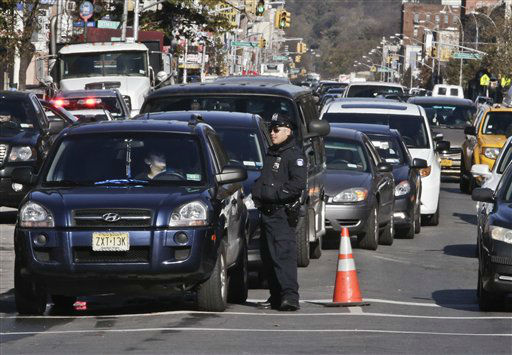 Police direct cars to gas pumps outside a gas station on Friday, Nov. 9, 2012 in the Brooklyn borough of New York.  Police were at gas stations to enforce a new gasoline rationing plan that lets motorists fill up every other day that started in New York on Friday morning. &#40;AP Photo&#47;Bebeto Matthews&#41; <span class=meta>(AP Photo&#47; Bebeto Matthews)</span>