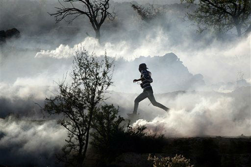 A Palestinian demonstrator runs through a cloud of tear gas during clashes against Israel&#39;s operations in Gaza Strip, outside Ofer, an Israeli military prison near the West Bank city of Ramallah, Thursday, Nov. 15, 2012.&#40;AP Photo&#47;Majdi Mohammed&#41; <span class=meta>(AP Photo&#47; Majdi Mohammed)</span>